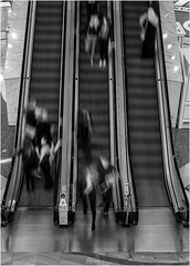 271/366 Escalation (Mister Oy) Tags: blackandwhite motion monochrome retail mall shopping mono movement escalator fujifilm weekly shoppers davegreen traffordcentre x100 oyphotos fujix100