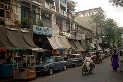 33-530 (ndpa / s. lundeen, archivist) Tags: nick dewolf nickdewolf 33 reel33 color photographbynickdewolf 1970s 1972 fall film 35mm winter 1973 asia vietnam southvietnam vietnamese southvietnamese saigon city citylife street streetlife candid streetphotography people building buildings sign signs store stores shop shops storefront storefronts traffic cars vehicles automobiles parkedcars tarps awnings car vehicle automobile taxi cab pedestrians woman youngwoman motorbike motorcycle scooter tanviet