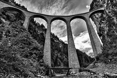 In High Regard (Woodacus) Tags: bridge blackandwhite bw white black alps monochrome stone alpes river mono switzerland europe arch walk under wiesen sbb hike viaduct alpine below desaturated alpen curve curved alpi hdr ffs mountainrange rhb cff landwasser rhätischebahn graubunden davosmonstein ef1740mmf4lusm filisur rhaetianrailway viafierretica ferroviaretica canoneos5dmarkii hdrefexpro