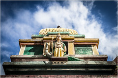 watching . (:: Blende 22 ::) Tags: trees pamplemousses tree bume baum blauerhimmel canoneos5dmarkii ef2470f28liiusm mauritius maskarenen sky sun temple hinduism color colorful roof figure clouds cloudy bewlkt hinduismus street religion