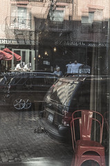 Reflecting Life In South Street Seaport Area NYC (nrhodesphotos(the_eye_of_the_moment)) Tags: dsc08102300 theeyeofthemoment21gmailcom wwwflickrcomphotostheeyeofthemoment reflections shadows window inverted man women car auto restaurant street chair cobblestone incadenscent bulbs doors fireescape brick glass umbrella tenements nyc manhattan streetscene southstreetseaport perspective cars autos transportation shopkeeper pedestrian