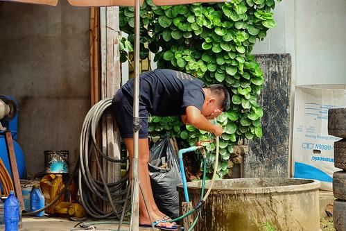 Washing up at repair shop,  Chiang Mai, Thailand.