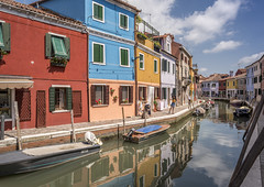 Colorful houses alongside canal in Burano (Sorin Popovich) Tags: burano italy house multicoloured architecture buildingexterior canal citylife colourimage day facade horizontal incidentalpeople italianculture moored mooringpost outdoors photography reflection rowingboat tradition tranquility traveldestinations veneto venetianlagoon city