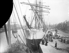 Queen Elizabeth at City Quay, Dublin (National Library of Ireland on The Commons) Tags: ireland horses dublin liverpool docks children manchester barrels ships belfast steam cobblestones cranes chq barefoot dumbarton hoops shipping masts winch carts urinals rigging pissoir queenelizabeth figurehead dockers glassnegative casks publictoilets leinster cityquay stacka robertfrench williamlawrence nationallibraryofireland lawrencecollection goodssheds cityofdublinsteampacketco svqueenelizabeth amcmillanson