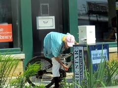IMG_8178 (kennethkonica) Tags: peoplepersons canonpowershot canon global random hoosiers outdoor talking candid street streetphotography marioncounty midwest america usa indiana indianapolis indy hat seniorcitizen oldwoman theindianapolisstar newspaperbox weeds window publiclibrary read newspaper elderly bike summer reflection cross city urban