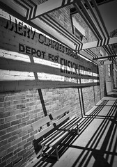 Ouyen VIC (phunnyfotos) Tags: phunnyfotos australia victoria vic mallee ouyen shadow shadows seat emptyseat sign paintedsign wall nikon d750 nikond750 ensignservices drycleaning laundryservices depot mervclarkesdrapery rural countrytown pergola shop drapery store bw mono monotone