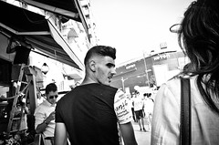 What Did You Just Say? (stimpsonjake) Tags: nikoncoolpixa 185mm streetphotography bucharest romania city candid blackandwhite bw monochrome lookingback man woman young face