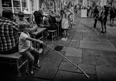Reaching out - street portrait (Daz Smith) Tags: dazsmith canon6d bw blackwhite blackandwhite bath city streetphotography people candid canon portrait citylife thecity urban streets uk monochrome blancoynegro mono cafe dining eat playing toy young boy