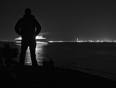 (The New Motive Power) Tags: city shadow sea blackandwhite man motion black reflection abandoned water silhouette ferry standing stars person lights glow moody bright fort military horizon victorian minimal historic deck isleofwight solent portsmouth passing outline distance fortress derelict nomansland defence canon7d