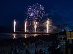 Watching Fire Flies (Steve Taylor (Photography)) Tags: night fence light black mauve purple fun people newzealand nz southisland canterbury christchurch newbrighton beach ocean pacific pier sea sky 5 5th 2015 bonfire crowd display firework november watching reflection silhouette smoky