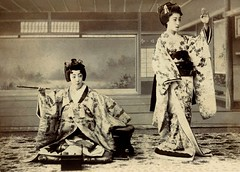 A Maiko in Two Poses 1900 (Blue Ruin1) Tags: japan standing japanese sitting dancing postcard coat maiko geiko armrest seated zabuton meijiperiod kiseru apprenticegeisha tobaccopipe floorcushion smokingbox hikizuri michiyuki trickphotograph trailingkimono kyosoku tobakobon