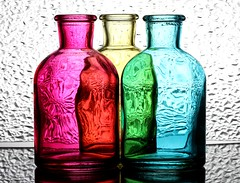 3 Bottles - 5 Colours (Karen_Chappell) Tags: colourful colours colour three refraction pink red green yellow blue white glass bottle bottles stilllife texture multicoloured 3