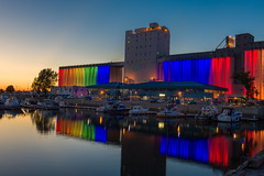 Bunge for gay pride (le cabri) Tags: gaypride grain silos quebeccity quebec rainbow light night longexposure parade flag gay landscape cityscape blue red purple port