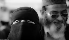 Behind every succesful woman ! (Neil. Moralee) Tags: street portrait england blackandwhite bw woman white man black london square eyes couple britain hijab trafalgar husband wife multicultural niqab burqa burka cancic neilmoraleenikon