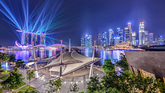 Theatrical Lights [Explored] (Scintt) Tags: show city travel trees light sky urban art tourism water festival skyline architecture night clouds marina buildings reflections way bay hall scenery singapore flickr ray cityscape colours open place theatre outdoor district air dramatic surreal science images fisheye beam explore esplanade laser getty cbd sands exploration 8mm financial mbs raffles shenton samyang defished scintillation explored scintt gettysingapore