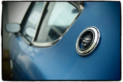Fairlady Z (Eric Flexyourhead) Tags: old blue canada detail car emblem japanese nissan bc bokeh britishcolumbia dirty richmond pinhole badge worn weathered vignette steveston patina datsun fairlady fragment 280z oxidized nissanfairladyz artfilter datsun280z olympusep1 panasoniclumix20mmf17