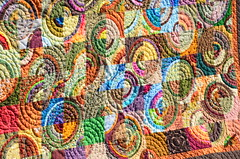 Out of This World quilt close up (Sewfrench) Tags: blue orange brown green fall colors yellow modern quilt scrappy scrapquilt drunkardspath handquilted scrapbuster bloggersquiltfestivalquilt