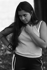 Watching (Poocher7) Tags: monochrome blackandwhite pople portrait candid prettygirl lovely beautiful trackpants tanktop watching darkhair longhair indian heart necklace watch