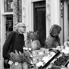 Where are the pineapples? (John Riper) Tags: johnriper street photography straatfotografie square vierkant bw black white zwartwit mono monochrome netherlands candid john riper canon 6d l 24105 harlingen friesland fryslan fruit greengrocery man woman looking pineapples