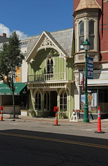 Whimsical Building  Mount Vernon, Ohio (Pythaglio) Tags: building structure historic commercial mount vernon ohio knox county twostory frame gothic revival board batten boardandbatten siding lancetarched windows balustrade bargeboards green sidewalk street cones barricade trees sky blue mtvernon