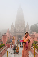 Pilgrim, Bodh Gaya (Marji Lang Photography) Tags: voyage morning travel pink people orange woman india mist flower colors rose misty fog temple image lotus pastel buddha buddhist indian femme foggy documentary atmosphere buddhism bouddha holy ethereal offering serene lovely tones sari brouillard pilgrim bodhi brume matin ambiance bouddhisme bihar bodhgaya lotusflower mahabodhi travelphotography bodhitree pastelcolors bouddhiste ef247028l indiansubcontinent offrande mahabodhitemple buddhistpilgrim canoneos5dmarkii foggylight travelanddocumentaryphotography marjilang mahabodhimahaviharatemple