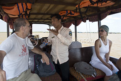 Cambodian tour guide talks with tourists on a boat to Tonle Sap Lake. (dkjphoto) Tags: travel lake fish tourism water river boat fishing asia cambodia seasia cambodian tour village tourist guide siemreap stilt tonlesap