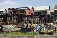 Fishermen repair fish pens in river next to houses on stilts. (dkjphoto) Tags: travel lake fish tourism home water pen river boat fishing asia cambodia seasia cambodian tour village fishermen tide tourist siemreap stilt raised tonlesap