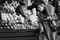 Fruit and Woman Carrying Flowers (John Westrock) Tags: seattle city flowers urban blackandwhite bw woman white money black vegetables fruit female contrast canon shopping downtown streetphotography 7d pikeplace fruitstand washingtonstate publicmarket 135f2l