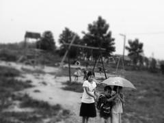 Caring (an vanhooren) Tags: child blackandwhite rain takingcare protect playground