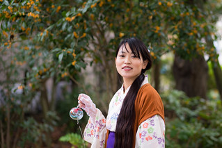 Young yukata woman walking in park with Japanese wind bell