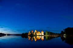 Trakai Castle at night (Julius Kielaitis Photography) Tags: old travel blue light red summer sky panorama lake reflection building brick tower castle history tourism nature water wall museum architecture night clouds landscape outdoors island countryside ancient exterior fort magic traditional gothic perspective culture kingdom landmark scene palace baltic medieval historic knight historical recreation lithuania vilnius trakai antiquity galve