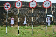 Galle, Sri Lanka 2016 (f.d. walker) Tags: asia galle srilanka streetphotography street sunlight shadow sun candidphotography candid color clothes colorphotography children contrast colors child city people person girl girls sign signs wall fort grass school schooluniform uniform skirt umbrella