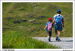 Boy and Girl hiking in the alps (Ilan Shacham) Tags: road flowers boy mountain alps girl beautiful grass walking landscape switzerland holding hands view hiking swiss scenic trail