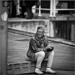 still waiting... (John Riper) Tags: johnriper street photography straatfotografie square vierkant bw black white zwartwit mono monochrome netherlands candid john riper canon rotterdam marine port worldportdays wereldhavendagen 6d 70200 l lady woman waiting sitting umbrella milano glasses