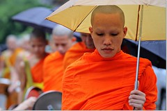 Walk the path of a carefree life, desiring nothing... (CK_Expresso) Tags: people orange umbrella walking focus dof path monk nothing laos raining carefree luang robes prabang desiring ckexpresso