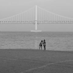 Beachgoers and Bridge in Busan (Mondmann) Tags: ocean bridge girls sea sky people bw beach water coast sand asia korea busan southkorea squarecrop rok pusan koreans eastasia republicofkorea beachgoers northeastasia mondmann canonpowershotg7x