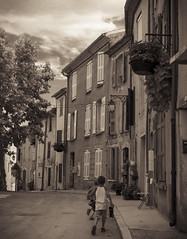 Temps de rentrer / Time to go home (CTfoto2013) Tags: vintage retro sepia nostalgie nostalgy street rue alley streetshot scenederue ruelle village france valensole paca alpesdehauteprovence ville town monochrome lumix gx7 panasonic ambiance mood architecture door porte lumiere light shadows ombre courbe curve mystere mystery provence calle callejon sky ciel clouds nuages outdoor road kids children enfants gamins personnages passants people
