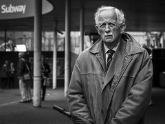 The Skin We Wear (Leanne Boulton) Tags: people monochrome urban street candid portrait portraiture streetphotography candidstreetphotography candidportrait eyecontact candideyecontact old age aged elderly man male face facial expression look emotion feeling eyes moustache leather jacket smart wrinkles skin tone texture detail depthoffield natural outdoor light shade shadow city scene human life living humanity society culture canon 7d 50mm black white blackwhite bw mono blackandwhite glasgow scotland uk