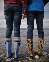 Best Friends (jakevanwinkle) Tags: ocean friends beach water hands boots tide pacificnorthwest fujifilm holdinghands pnw x10 filmemulation