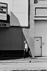 Between Light and Dark (ahh.photo) Tags: street light shadow blackandwhite bw man film dark walking 1 orlando nikon downtown kodak trix f100 monotone 400tx 35mmfilm shade sigma85mmf14
