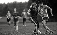 Girl vs Boy (Poocher7) Tags: monochrome blackandwhite action scoccer football field ball soccerball grass players girl boy fighingfortheball fight sports fieldsports domination nike shorts stripedpants blondegirl curlyhair youth portrait candid people cleats ftbol  voetbal putbol fusball  calcio   bng