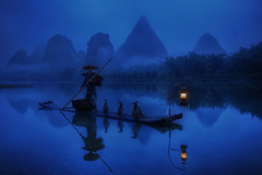 Cormorant Fisherman (TheFella) Tags: china morning travel blue trees light mist mountain man mountains slr water lamp hat fog digital photoshop sunrise canon river cormorants person eos dawn liriver li photo fisherman asia cloudy guilin yangshuo fineart hill chinese pole hills explore photograph figure processing limestone lone 5d cormorant bluehour dslr  karst fareast hdr highdynamicrange lijiang southchina mkii guangxi markii eastasia  postprocessing travelphotography ricehat lijiangriver  photomatix cormorantfisherman explored cooliehat  thefella paddyhat 5dmarkii  conormacneill thefellaphotography