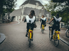 Angel Wings (Rolling Spoke) Tags: bike bicycle bici bicicletta bicicleta ciclismo fiets velo street streetphotography yellow bikes angel wings road cobbled bridge bachelorette party girl girls grachtengordel amsterdam
