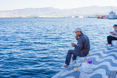 Man Tying Fishing Knots with Hands and Mouth in Front of Sea (danliecheng) Tags: izmir turkey bags bank editorial fishing hands harbor hobby jacket jeans knots lifestyle lines man morning mouth sea sit sportsshoes stool summer tie travel visit worn