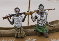 Young Karo Men With White Painted Faces And Chests Holding Kalashnikov Rifle In Omo River , Omo Valley Ethiopia (Eric Lafforgue) Tags: africa people water horizontal standing river rifle picture tribal photograph transportation blackpeople warrior omovalley ethiopia tribe carvedwood navigation adultsonly woodcarving ak47 colorphoto carbine nomadic kalashnikov lookingatcamera mosin nagant omoriver indigenousculture snnpr southernethiopia truepeople exterioroutdoors korcho omotic southernnationsnationalitiesandpeoplesregion blackethnicity karakarokerre bodypaintingnaturalpatterndesignritualbodyart whitepaintchalkpatternsdesignbodypaintingritualpow whitepaintchalkpatternsdesignbodypaintingritualpowder ak47ak47weaponfirearmlethalriflefiregunkalashn warwarfareconflictconfrontationencounterclashweapons ethiopianomovalley abyssiniahornofafrica landleasinglandgrabgiveawayexpropriationseizuredispo landleasinglandgrabgiveawayexpropriationseizuredispossessionrepossessiontaking warwarfareconflictconfrontationencounterclashweaponsfiregunsriflesviolence ak47ak47weaponfirearmlethalriflefiregunkalashnikov canoeemptytrunkdugout conflictconfrontationwarwarfare twomaturemenonly ethio8298 southernnationsnationalitiesandpeoplesregionsnnpr