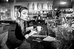 Coffee break (Jeff Krol) Tags: street urban blackandwhite bw woman coffee girl monochrome amsterdam bar reflections eyes noir break fuji noiretblanc candid laptop streetphotography finepix headphones fujifilm contact blanc coffeebreak beats 2012 x10 dscf4292 jeffkrol fujix10 fujifilmfinepixx10