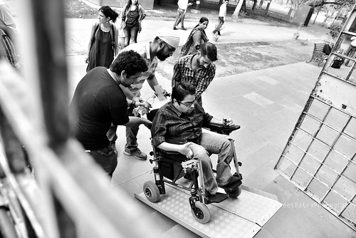 A traveller who is a wheelchair user being assisted by our trained volunteers. We customize our tours depending on the specific needs of our travellers.