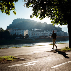 sunny morning in Salzburg (.martinjakab) Tags: person x100t fujifilm austria square kapuzinerberg backlight sterreich sunstar streetphotography 1 walking fluss river