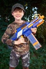 AubreyDayBefore9-7485 (labrossephotography) Tags: boy child 9yo nerfgun camouflage camo strobist smile kid fun outside people portrait person birthday cute grin