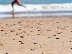 Last summer (S. de Cima) Tags: sea espaa beach valencia canon lens mar spain sand waves child stones playa olympus arena 55mm mf fl manual nio olas omd piedras f12 m43 elsaler em5